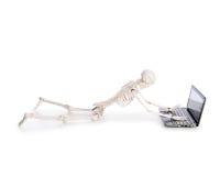 Skeleton working. On laptop on white Royalty Free Stock Photos
