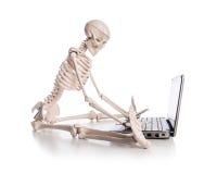 Skeleton working. On the laptop Royalty Free Stock Photo