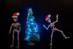 Christmas Spirit. Skeletons dancing around a Christmas Tree with lights stock photos