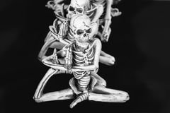 Skeletons in a row doing yoga with one foot up under their arms. Sitting in a row - black and white isolated against black background royalty free stock photos