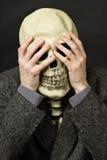 Skelett, das seine Augen abdeckt Stockbilder