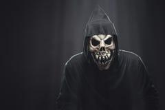 Skelett in einer schwarzen Robe, die unter Strahlen steht Stockfotografie