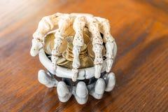 2 skelett- händer som rymmer bunken av mynt för halloween royaltyfria bilder