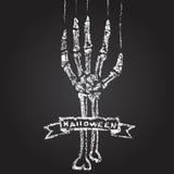 Skelett- hand med krita på en svart tavla och a Arkivbilder