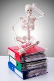 Skelett mit Stapel von Dateien gegen Steigung Stockbilder
