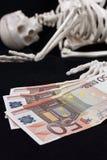 Skelett und Geld Stockfotografie