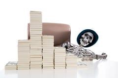 Skelettet av rikeman som absolut ligger bak en hög av pengar Arkivfoto