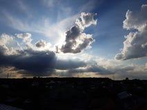 Sken för ljusa strålar till och med mjuka moln för solnedgång arkivbild