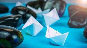 Skepp för ledning för ledarskapvitbokfartyg vaggar ytterligare mellan abstrakt begrepp stenar på blå bakgrund Ljus blossar rätt b Arkivfoto