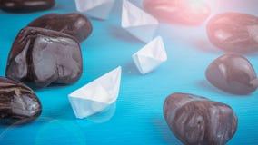 Skepp för ledning för ledarskapvitbokfartyg vaggar ytterligare mellan abstrakt begrepp stenar på blå bakgrund Ljus blossar rätt b Arkivbild