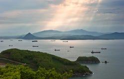 Skepp i fjärden som tänds av strålarna av solen Nakhodka fjärd Östligt (Japan) hav 21 05 2014 arkivfoton
