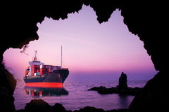 Skepp med behållareblick till och med grottan Arkivbilder