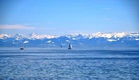 Skepp på den blåa sjön, blå himmel för frikänd, och snöig berg, Boden sjö och Schwitzer fjällängar, sikt från Insel Mainau på vår Royaltyfria Foton