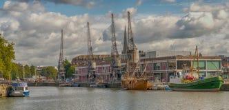 Skepp som förtöjas i Bristol Docks med M Shed och kranar, royaltyfri foto