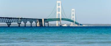 Skeppet passerar under den Mackinac bron i Michigan arkivbilder
