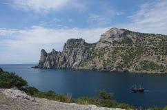 Skeppet seglar på havet mot bakgrunden av berg arkivbilder