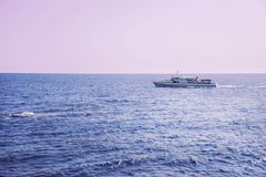 Skeppet seglar på havet under en rosa solnedgång Royaltyfri Bild