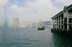 Skeppet seglar till pir av Victoria Harbor med bakgrund av staden av Hong Kong Arkivbild