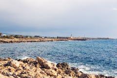 Skepphaveriet som omges av havet, vinkar på stranden, Cypern arkivfoton