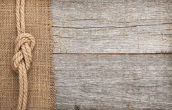 Skepprepet på trä och säckväv texturerar bakgrund Arkivfoto