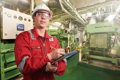 Skepps mekaniker nära marin- diesel- generatorer på en handelsfartyg i maskinrummet arkivfoton