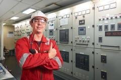 Skepps mekaniker nära marin- diesel- generatorer på en handelsfartyg i maskinrummet royaltyfria bilder