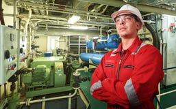 Skepps mekaniker nära marin- diesel- generatorer på en handelsfartyg i maskinrummet royaltyfri foto