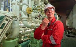 Skepps mekaniker nära marin- diesel- generatorer på en handelsfartyg i maskinrummet fotografering för bildbyråer