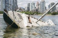 Skeppsbrott framme av en stad Fotografering för Bildbyråer
