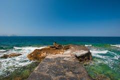 Skeppsbruten pir för stenpir azur yttersida av vatten arkivbild