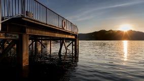 Skeppsdocka på sjön och berget på solnedgången eller soluppgång Arkivbilder