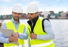 Skeppsdockaarbetare och arbetsledare som kontrollerar behållaredata Arkivfoto