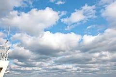 Skeppstrukturer, master, antenner, tratt, skeppwheelhouse mot den blåa himlen och moln arkivbild