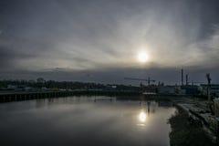 Skeppsvarven på floden mättar, som solen stiger ned långsamt på horisonten fotografering för bildbyråer