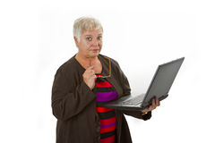 Skeptic female senior with laptop. Female senior with laptop - isolated on white background Royalty Free Stock Image