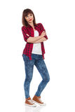 Skeptic Girl Looking Away Full Length. Young woman in red lumberjack shirt, jeans and brown sneakers standing with arms crossed and looking away. Full length Stock Photography