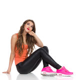 Skeptic Girl Looking Up. Smiling young woman in orange shirt, black leather trousers, pink sneakers sitting on a floor and looking up. Full length studio shot Stock Image