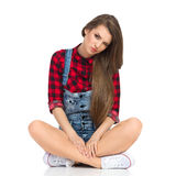 Skeptic Girl Sitting With Legs Crossed. Young woman in red lumberjack shirt, jeans shorts and white sneakers sitting on a floor with legs crossed, looking at Royalty Free Stock Photography