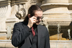 Skeptic handsome gentleman in a suit adjusting glasses - architectonic background.  Stock Photo
