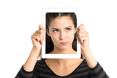 Skeptic. Isolated image of a young girl holding a tablet with a skeptical face over white Royalty Free Stock Photo