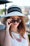 Skeptic. A pretty girl gazes over the rim of her sunglasses in skepticism Royalty Free Stock Photo