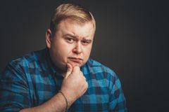 Skeptic, unsure, uncertain, doubts concept. Fat guy looking sceptical Stock Photography
