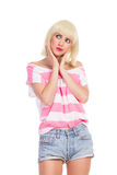 Skeptic woman. Grimacing blonde young woman holding hands on chin and looking away. Three quarter length studio shot isolated on white Stock Image