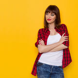 Skeptic Woman Looking Away. Grimacing young woman in red lumberjack shirt and jeans posing with arms crossed and looking away. Three quarter length studio shot Stock Image