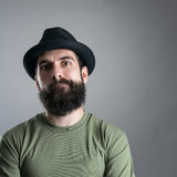 Skeptical bearded hipster staring at camera. Headshot close up portrait over gray studio background with vignette Stock Image