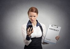 Skeptical businesswoman holding contract looking on smartphone Stock Photo