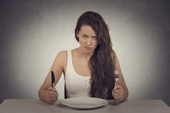 Skeptical dieting woman tired of diet restrictions looking frustrated. Young skeptical dieting woman tired of diet restrictions looking at camera sitting at Royalty Free Stock Images