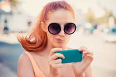 Skeptical, doubtful shocked anxious scared young girl looking at phone stock photography