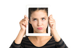 Skeptical face in gadget. Isolated image of a girl holding a tablet with a skeptical face over a white background Royalty Free Stock Image