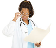 Skeptical Female Doctor. Holding a chart, looks over her glasses at you.  Isolated on white Royalty Free Stock Image